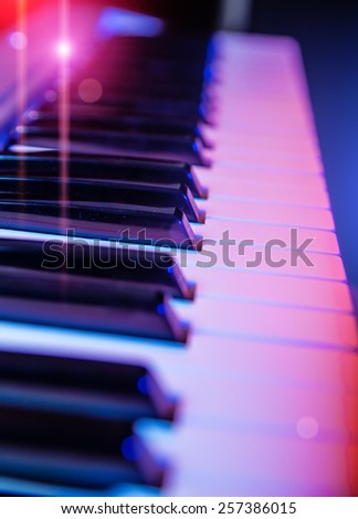 Sparks of light around the keyboard of synthesizer - stock photo