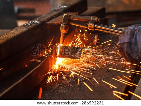 Sparks while cutting steel in the factory. - stock photo