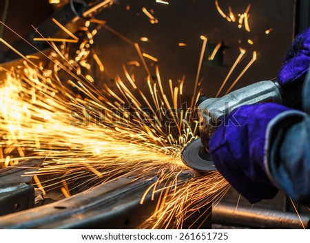 Sparks while grinding iron in factory - stock photo