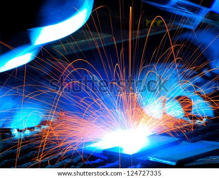 sparks while welder uses torch to welding - stock photo