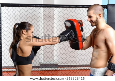 Sparring fight. Female mixed martial art fighter training with a couch in fighting cage - stock photo