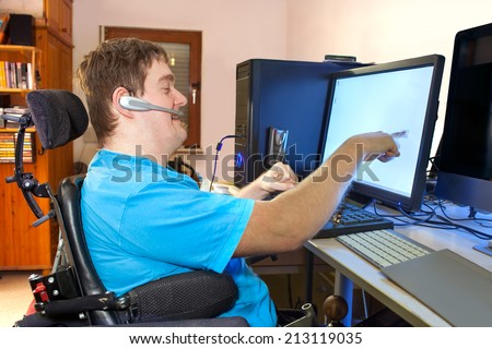 Spastic young man with infantile cerebral palsy caused by a complicated birth sitting in a multifunctional wheelchair using a computer with a wireless headset reaching out to touch the touch screen - stock photo