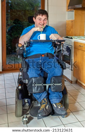 Spastic young man with infantile cerebral palsy caused by complications at birth sitting in a multifunctional wheelchair enjoying a mug of beverage drinking through a straw - stock photo