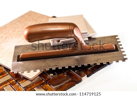 Spatula and ceramic tiles for walls and floors on a white background - stock photo