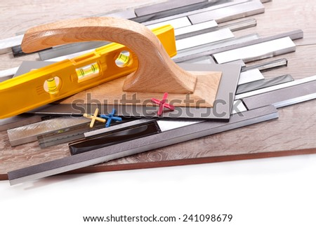 Spatula, ceramic tiles for floors and walls,level, crosses on a white background - stock photo