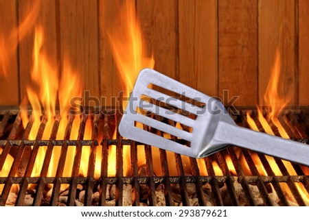 Spatula Close-up On The Hot Flaming BBQ Grill And Brown Wood Siding Wall In  The Background. Cookout or Picnic or Summer Outdoor Party Concept And Idea, With Copy Space - stock photo
