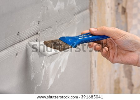 spatula with plaster in hand  - stock photo