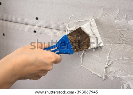 spatula with plaster in hand during plastering walls, closeup - stock photo