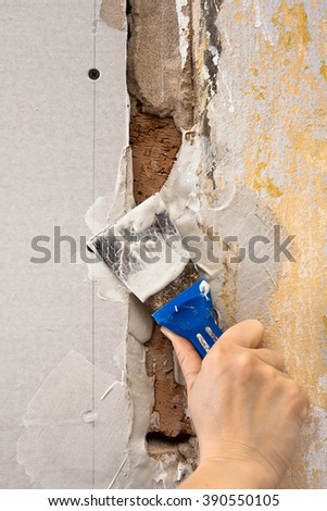 spatula with plaster in hand during repair - stock photo