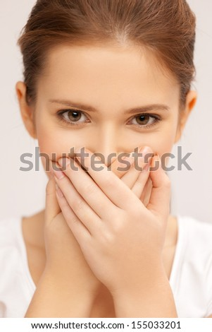 speak no evil concept - face of beautiful teenage girl covering her mouth - stock photo