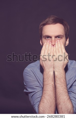 Speak no evil concept - Face of men covering his mouth on Black background. old film toned - stock photo