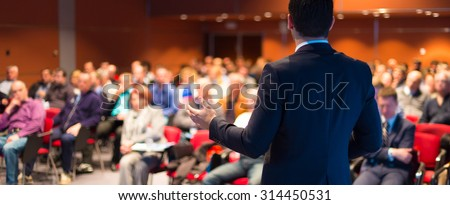 Speaker at Business Conference with Public Presentations. Audience at the conference hall. Entrepreneurship club. Rear view. Panoramic composition. Background blur. - stock photo