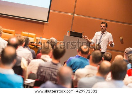 Speaker at Business Conference with Public Presentations. Audience at the conference hall. Entrepreneurship club. Rear view. Horisontal composition. Background blur. - stock photo