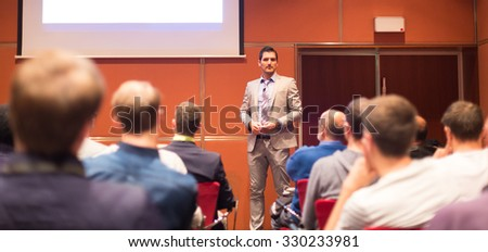 Speaker Giving a Talk at Business Meeting. Audience in the conference hall. Business and Entrepreneurship concept. Panoramic compozition suitable for banner. - stock photo