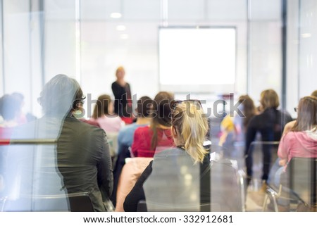 Speaker Giving a Talk at Business Meeting. Trough the glass rear view of audience in lecture room.  Business and Entrepreneurship - stock photo