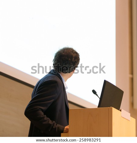 Speaker giving talk on podium at Business Conference. Business and Entrepreneurship. White copy space on screen. - stock photo