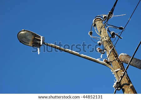 speaker, lamps and electrical cables isolated on blue winter sky covered by snow