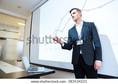 Speaker standing and lecturing on business conference in meeting hall