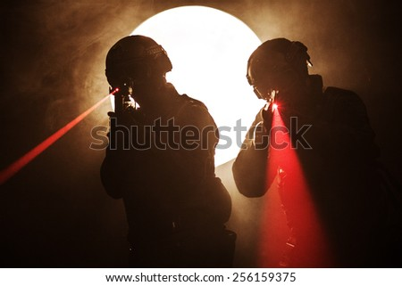 Spec ops police officers SWAT in the smoke and fire with laser sights - stock photo