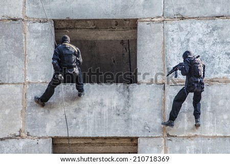 Spec ops soldier in face mask during rope exercises with weapons - stock photo