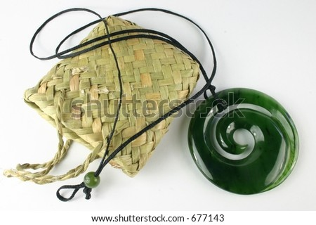 Special carved maori nephrite jade (pounamu) pendant from New Zealand with woven kit bag - stock photo