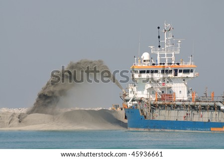 Special dredge ship pipe pushing sand to create new land in Dubai, United Arab Emirates - stock photo