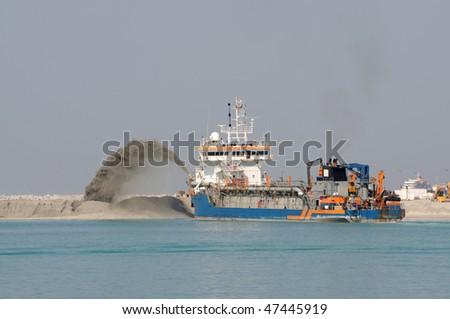 Special dredge ship pushing sand to create new land in Dubai, United Arab Emirates - stock photo
