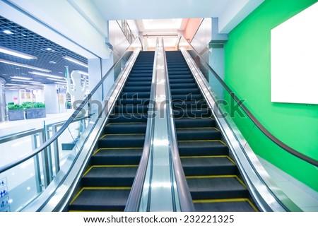Special escalator in modern mall with blank billboard  - stock photo