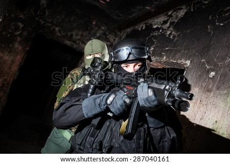 Special forces/anti-terrorist unit or contractor team during night CQB mission/operation (color toned image, very harsh lighting is used on this shot to underline the atmosphere of night mission) - stock photo