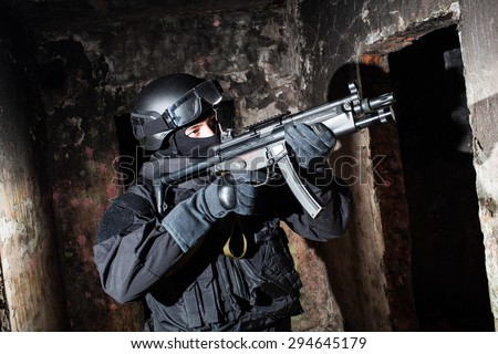 Special forces/anti-terrorist unit policeman or contractor during night CQB mission/operation (color toned image, very harsh lighting is used on this shot to underline the atmosphere of night mission) - stock photo