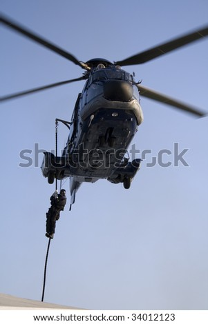Special forces member descending on rope from a helicopter (a French made AS 332 L1 Super Puma Euro Copter) - stock photo