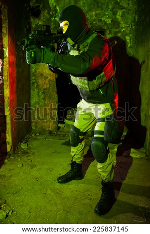 Special forces soldier/anti-terrorist unit policeman or contractor during night CQB mission/operation (red and green light for underline the atmosphere) - stock photo