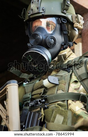 Special forces soldier during a black tactical exercises. Army Soldier  in full tactical gear with weapons  and gas mask. Real situation. - stock photo