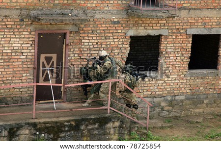 Special forces soldier during a black tactical exercises. Army Soldier  in full tactical gear with weapons  and gas mask. Intrusion inside the building after the detonation of an explosive. - stock photo