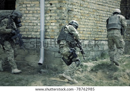 Special forces soldier during a black tactical exercises. Army Soldier  in full tactical gear with weapons  and gas mask. Real situation, action. - stock photo