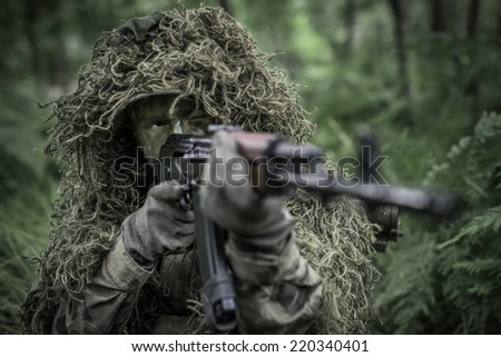 Special forces soldier in heavy camouflage hidden in forest, aiming with assault rifle - focus on eyes - stock photo