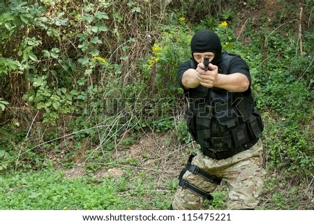 Special Forces soldier pointing a weapon directly into the lens - stock photo