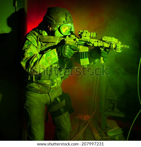 Special forces soldier with gas mask during the night mission (red and green light for underline the atmosphere) - stock photo