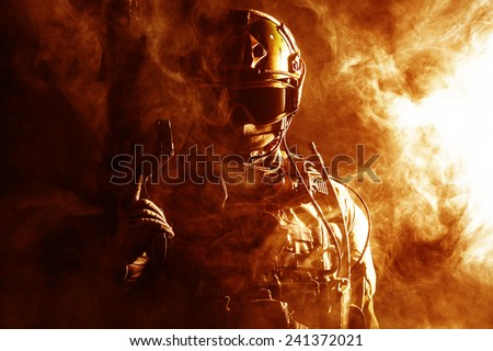 Special forces soldier with rifle in the fire - stock photo