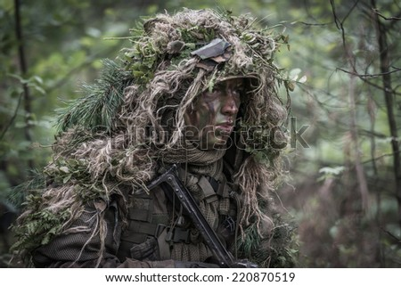 special forces warrior wearing heavy camouflage, moving silently through forest. - stock photo
