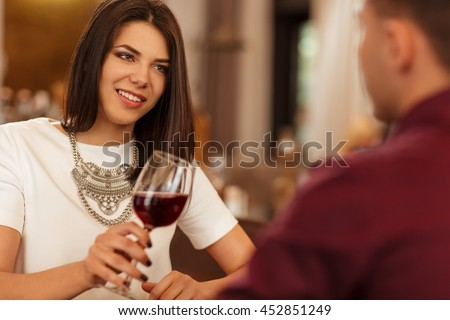 Special moments together. Beautiful young woman in love toasting her glass with her boyfriend at the dinner in the local restaurant  - stock photo