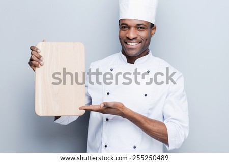 Special offer from chef. Confident young African chef in white uniform holding wooden cutting board and pointing it with smile while standing against grey background - stock photo
