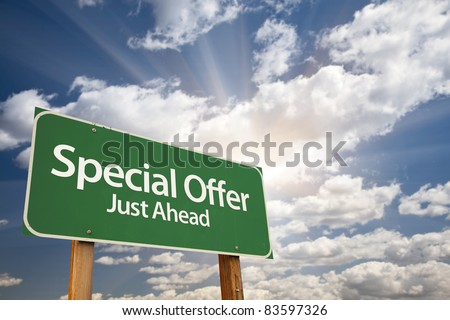 Special Offer, Just Ahead Green Road Sign Over Dramatic Sky, Clouds and Sunburst. - stock photo