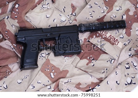 special operation handgun with silencer on camouflage background - stock photo