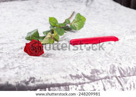 Special romantic Valentines gift of a single long-stemmed red rose and gift-wrapped red present lying on the bed on the white bedspread - stock photo