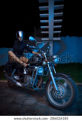 Special toned photo, unidentified biker girl sits on a chopper motorcycle, night view