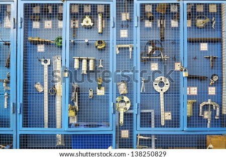 Special tools for car repairs are beyond blue lattice in closet. - stock photo