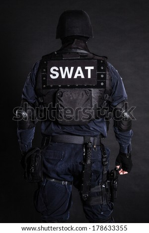 Special weapons and tactics (SWAT) team officer on black background shot from behind - stock photo