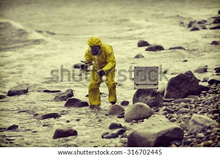 specialist in protective suit taking sample of water to container on rocky shore - stock photo