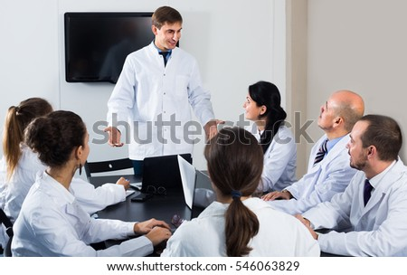 Specialists in white overalls and professor having discussion of research work